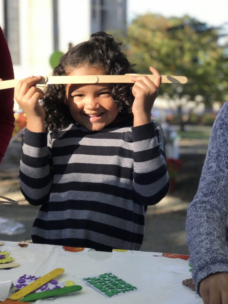 A little girl displays her craft proudly at an outdoor community event